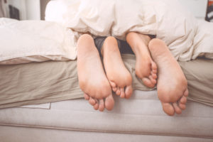 Feet couple on the bed.
